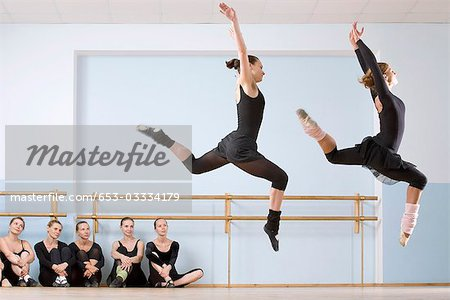 Two ballerinas leaping through the air as others look on Stock Photo - Premium Royalty-Free, Image code: 653-03334179