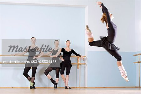 A ballerina leaping through the air as three other women look on Stock Photo - Premium Royalty-Free, Image code: 653-03334183