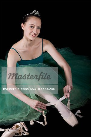 A ballet dancer wearing a costume tying her pointe shoe Stock Photo - Premium Royalty-Free, Image code: 653-03334246