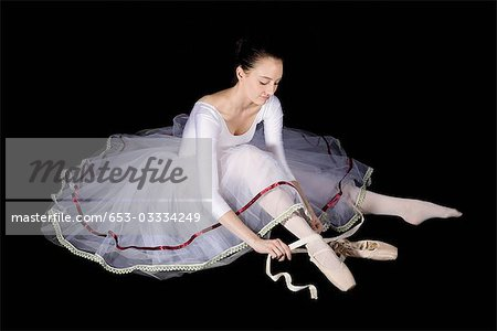 A ballet dancer tying her pointe shoe Stock Photo - Premium Royalty-Free, Image code: 653-03334249