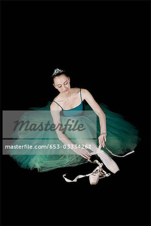 A ballet dancer wearing a costume tying her pointe shoe Stock Photo - Premium Royalty-Free, Image code: 653-03334262
