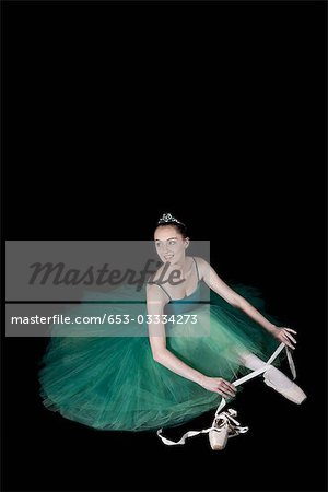 A ballet dancer wearing a costume tying her pointe shoe Stock Photo - Premium Royalty-Free, Image code: 653-03334273