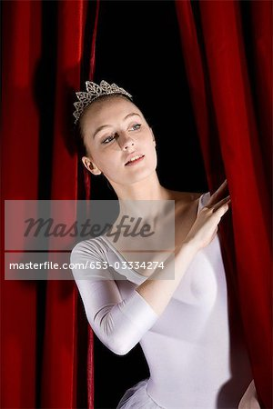 A ballet dancer peeking through a stage curtain, front view Stock Photo - Premium Royalty-Free, Image code: 653-03334274