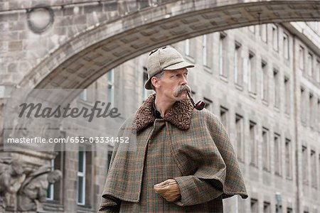 A man dressed up as Sherlock Holmes standing under a building arch looking away Stock Photo - Premium Royalty-Free, Image code: 653-03334452