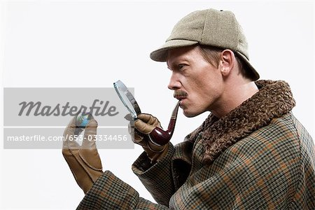 A man dressed up as Sherlock Holmes looking at a tiny globe through a magnifying glass Stock Photo - Premium Royalty-Free, Image code: 653-03334456