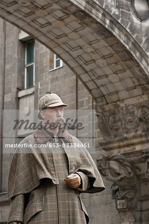 A man dressed up as Sherlock Holmes standing under a building arch looking away Stock Photo - Premium Royalty-Free, Image code: 653-03334461