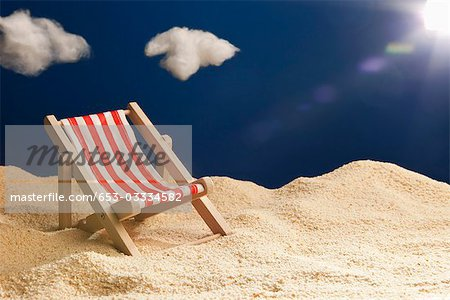 A miniature beach chair in sand Stock Photo - Premium Royalty-Free, Image code: 653-03334582