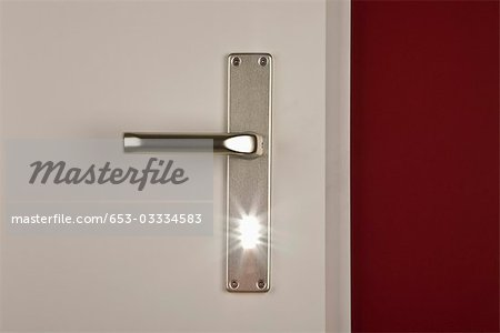 Detail of a light shining through the keyhole of a door Stock Photo - Premium Royalty-Free, Image code: 653-03334583