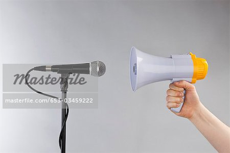 A hand holding a megaphone to a microphone Stock Photo - Premium Royalty-Free, Image code: 653-03459222