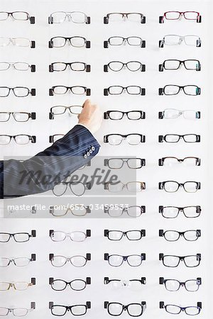 A human hand choosing a pair of glasses in an eyewear store Stock Photo - Premium Royalty-Free, Image code: 653-03459533