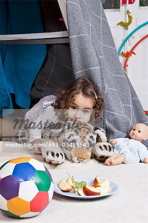 A young girl playing with a stuffed animal in a fort Stock Photo - Premium Royalty-Free, Image code: 653-03459549