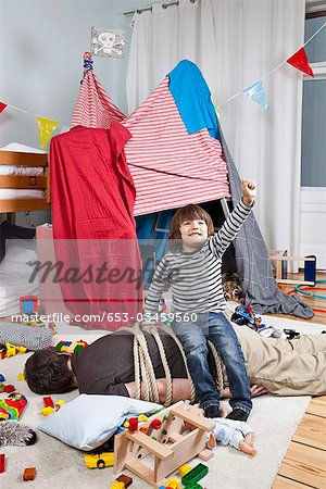 A young boy sitting on a tied up man in a child's playroom Stock Photo - Premium Royalty-Free, Image code: 653-03459560