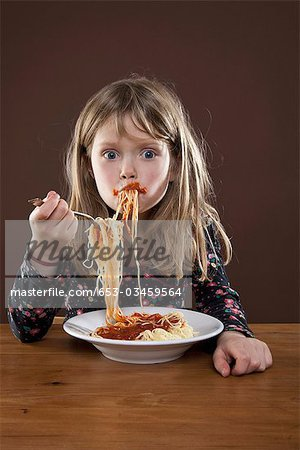 A young girl shoving spaghetti messily into her mouth, studio shot Stock Photo - Premium Royalty-Free, Image code: 653-03459564