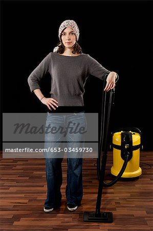 A Woman Standing Next To A Vacuum Cleaner Stock Photo - Premium Royalty-Free, Image code: 653-03459730