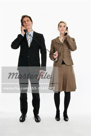Two business people using phone receivers connected with the same cord Stock Photo - Premium Royalty-Free, Image code: 653-03459972