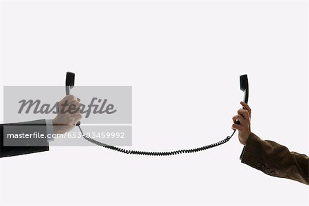 Two business people holding telephone receivers connect with the same cord Stock Photo - Premium Royalty-Free, Image code: 653-03459992