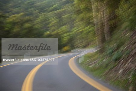 A road curving around a hillside, blurred motion