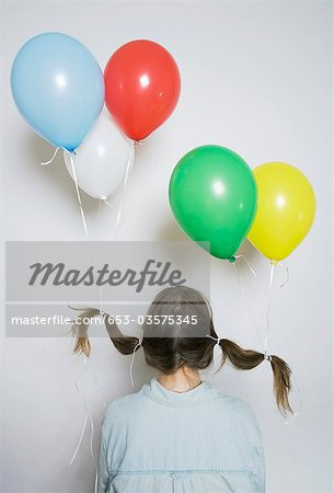 Rear view of a girl with helium balloons tied to her pigtails Stock Photo - Premium Royalty-Free, Image code: 653-03575345