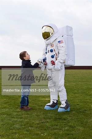 A boy shaking hands with an astronaut Stock Photo - Premium Royalty-Free, Image code: 653-03575362