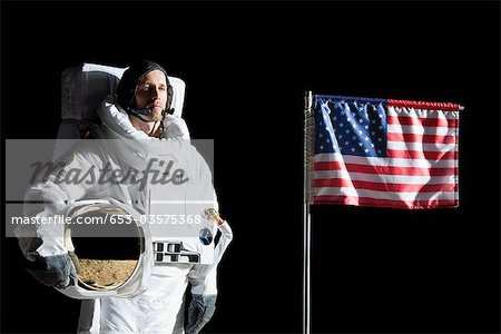 An astronaut holding his helmet standing next to an American flag, portrait Stock Photo - Premium Royalty-Free, Image code: 653-03575368