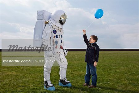 A boy holding out a balloon to an astronaut Stock Photo - Premium Royalty-Free, Image code: 653-03575373