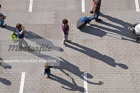 A group of people walking through a parking lot Stock Photo - Premium Royalty-Free, Image code: 653-03613216