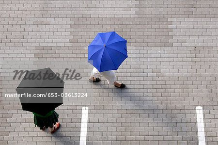 Two women with umbrellas walking through a parking lot Stock Photo - Premium Royalty-Free, Image code: 653-03613224