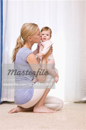A mother kissing her baby daughter Stock Photo - Premium Royalty-Free, Image code: 653-03705857