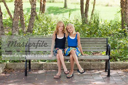 Two Girls legs crossed on a bench Stock Photo - Premium Royalty-Free, Image code: 653-03706040