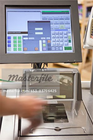 A cashier scanning groceries at a supermarket, focus on hand Stock Photo - Premium Royalty-Free, Image code: 653-03706425