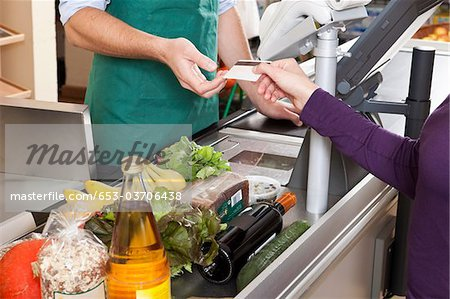 A customer handing a cashier a credit card at the supermarket Stock Photo - Premium Royalty-Free, Image code: 653-03706438