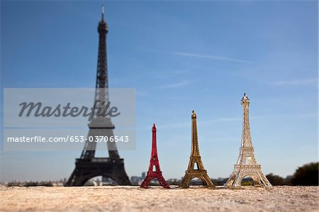 Three Eiffel Tower replica souvenirs next to the real Eiffel Tower, focus on foreground Stock Photo - Premium Royalty-Free, Image code: 653-03706543
