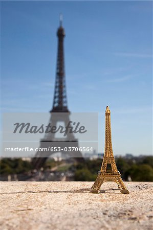 One Eiffel Tower replica souvenir next to the real Eiffel Tower, focus on foreground Stock Photo - Premium Royalty-Free, Image code: 653-03706564