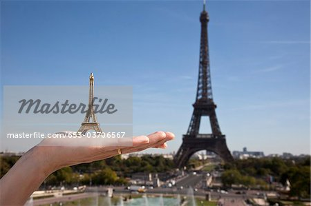 A woman holding an Eiffel Tower replica souvenir next to the real Eiffel Tower, focus on hand Stock Photo - Premium Royalty-Free, Image code: 653-03706567
