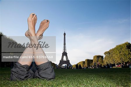 A woman laying in grass by Eiffel Tower, focus on feet Stock Photo - Premium Royalty-Free, Image code: 653-03706568