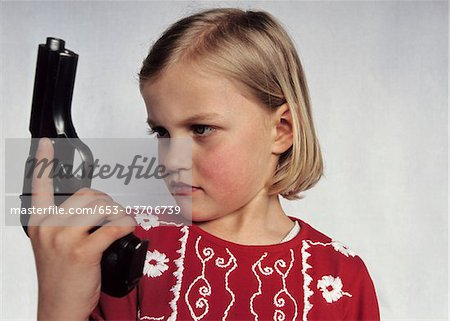 A young girl holding a gun Stock Photo - Premium Royalty-Free, Image code: 653-03706739