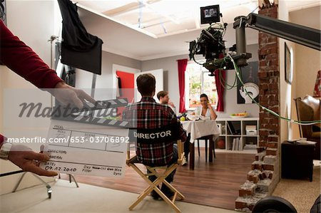A director on a film set watching actors perform a scene Stock Photo - Premium Royalty-Free, Image code: 653-03706892