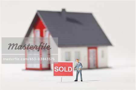 A miniature real estate agent figurine standing next to a SOLD sign Stock Photo - Premium Royalty-Free, Image code: 653-03843575