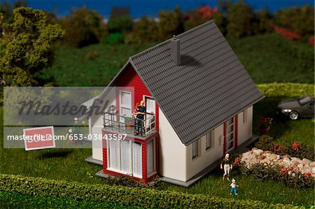 A diorama of a miniature house with a family of figurines and a SOLD sign Stock Photo - Premium Royalty-Free, Image code: 653-03843597