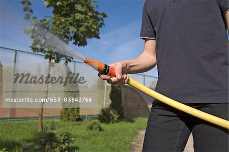 A teenage boy spraying a garden hose in a backyard, focus on hand Stock Photo - Premium Royalty-Free, Image code: 653-03843766
