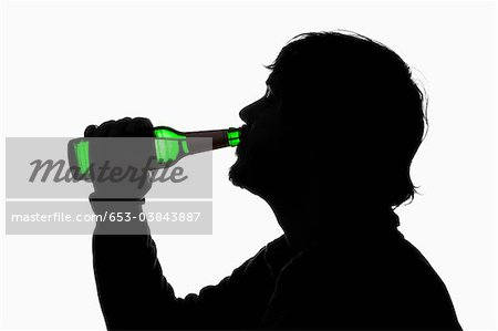 A silhouetted man drinking beer from a bottle Stock Photo - Premium Royalty-Free, Image code: 653-03843887