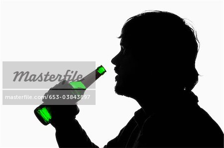 A silhouetted man about to drink from a beer bottle Stock Photo - Premium Royalty-Free, Image code: 653-03843897