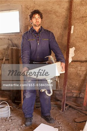 A construction worker carrying a sink at a building site Stock Photo - Premium Royalty-Free, Image code: 653-03843986