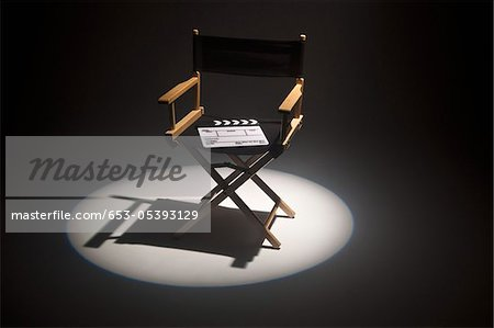 A spot lit directors chair and a clapper board Stock Photo - Premium Royalty-Free, Image code: 653-05393129