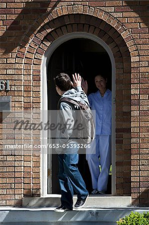 Son and Mother waving goodbye to each other at front door as son leaves house Stock Photo - Premium Royalty-Free, Image code: 653-05393266