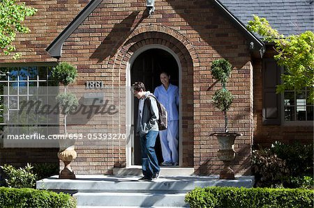Smiling Mother stands at front door of house as son departs Stock Photo - Premium Royalty-Free, Image code: 653-05393270