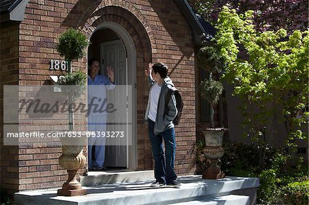 Son and Mother waving goodbye to each other at their front door as son leaves house Stock Photo - Premium Royalty-Free, Image code: 653-05393273