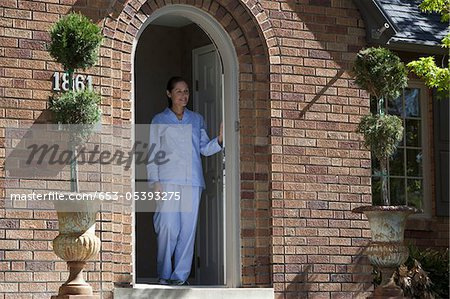 Smiling woman wearing Pajamas leans on front door and looks out Stock Photo - Premium Royalty-Free, Image code: 653-05393275