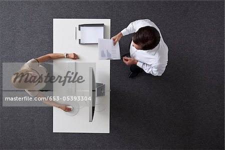A businessman giving papers to a businesswoman sitting at a desk, overhead view Stock Photo - Premium Royalty-Free, Image code: 653-05393304