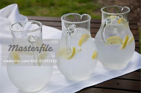 Three pitchers of ice water with lemon slices Stock Photo - Premium Royalty-Free, Image code: 653-05393322